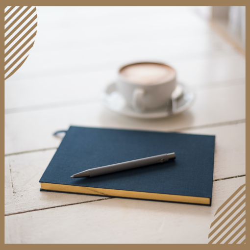 A notebook with a pen and a cup of Cacao.