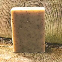 An unboxed bar of soap. It is grey with black grains in it,