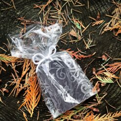 A soap wrapped in a transparent, pattered cello bag. The pattern is of silver lace.