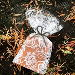 A soap wrapped in a transparent, pattered cello bag. The pattern is of white lace.