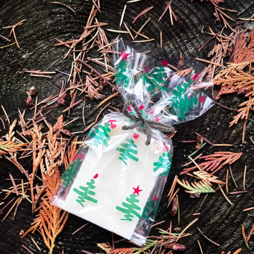 A soap wrapped in a transparent, pattered cello bag. The pattern is of light green trees with red baubles at their tops.