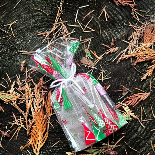A soap wrapped in a transparent, pattered cello bag. The pattern is of red and green triangle-shaped trees.