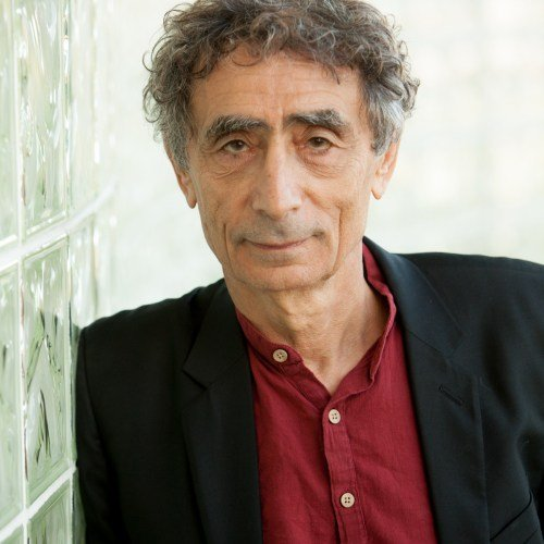 Dr. Gabor Maté leaning against a glass wall smiling.